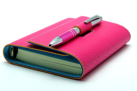 Personal Organizer in Pink Color With Ballpoint Pen on White Background