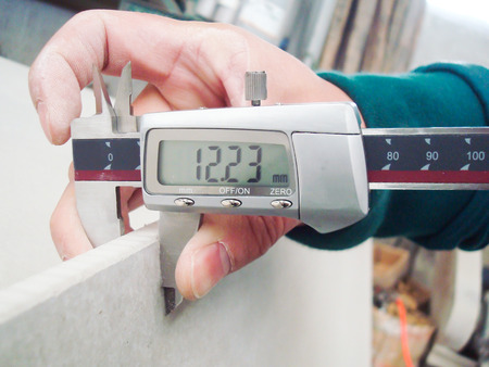 Worker Measuring the Level of Gypsum Board Thickness for Quality  Stock Photo