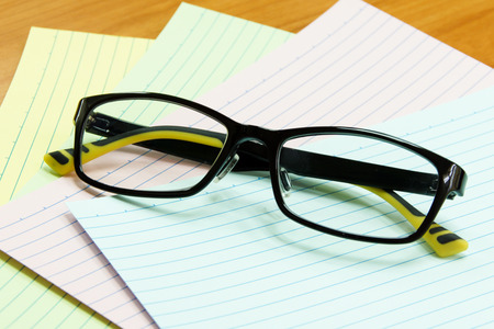 Eyeglasses and Note Paper on Wooden Office Table Stock Photo