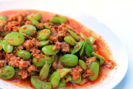 Stir-fried of Spicy Pork with Stink Beans on white background photo