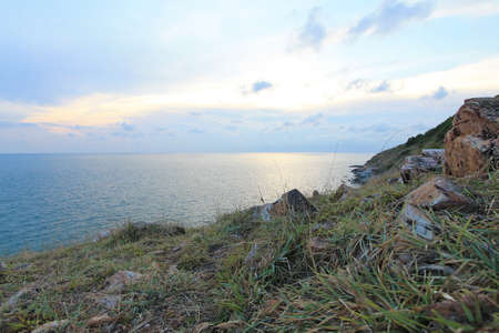 Clear sky over the blue sea with rock and grass in the foreground