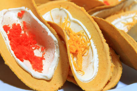 Stuffed cripsy egg-crepe with white cream and topping in Thai style