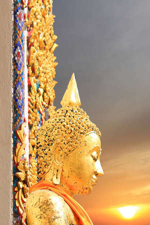 Side view of the ancient golden buddha face against sunrise Stock Photo