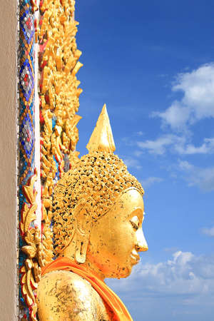 Side view of the ancient golden buddha face against blue sky
