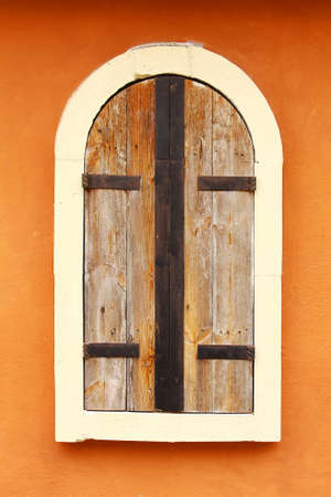 Closed Wood window with white frame on the old orange wall in ancient style Stock Photo