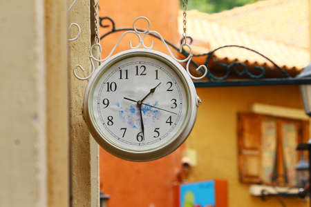 The round street watch hanging outdoor on the wall
