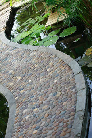 d       cor: Garden stone path over the pond with lotus in the garden Stock Photo
