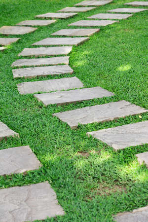 Garden stone path with green grass in the garden Stock Photo