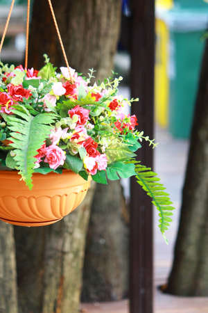 Clay pot planter filled with artificial flowers hanging for decorating places
