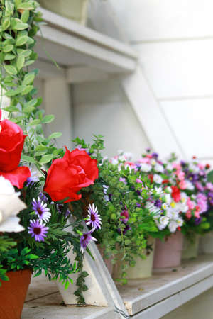 Colorful bouquets of artificial flowers in the pot planters decorated on the white wooden shelf