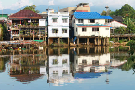 Old house buildings along Chantaboon river bank with their reflection reflected of the river