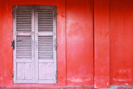 Black old door on a red wall background Stock Photo