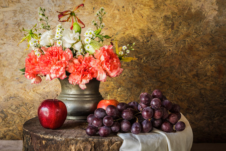 Still life with Fruits were placed together with a vase of flowers beautifully. Stock Photo