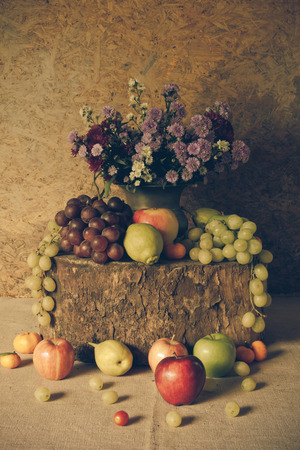 Still Life Fruits were placed on the timber with a beautiful vase of flowers. photo