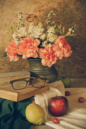 Still life with glasses resting on the book with fruits and flowers in a vase. photo