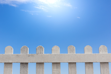 old white wooden fence on a blue sky and sea background