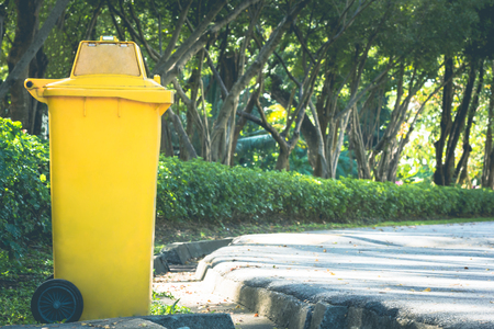 yellow bin in the park in autumn used for placing text and illustrations. Stock Photo