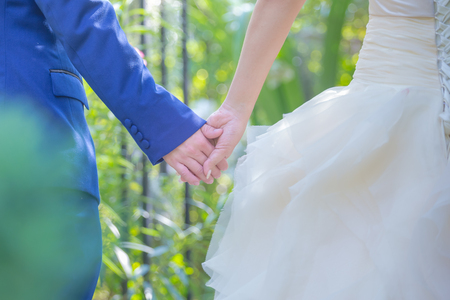 Groom holding brides hand in outdoors wedding, holding hands newlyweds for an illustration of the wedding ceremony.