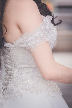 bodice: The back of a bride with a beautiful wedding dress embroidered with delicate patterns on fabric.