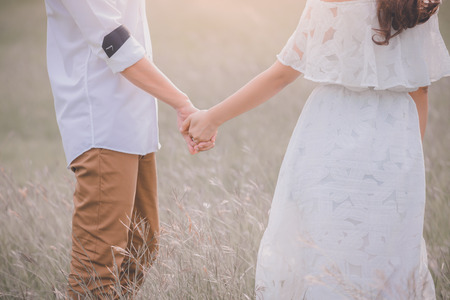 Young express love with a handshake as a symbol of love and marriage.