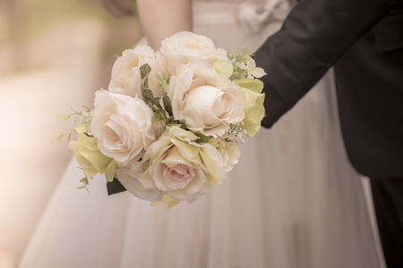 Newlyweds with a bouquet of beautiful flowers is the symbol of love and marriage.