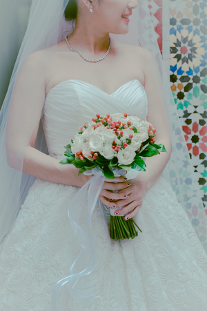 attribute: Close up view of beautiful colorful wedding bouquet in the hand of a bride and symbol of love