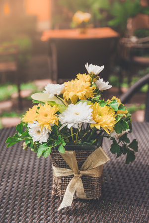 Beautiful chrysanthemum yellow and white in a vase put on the table. Reklamní fotografie