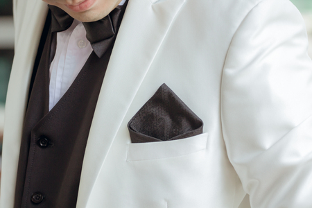 A handkerchief in a white suit of a man who is about to be the bridegroom.