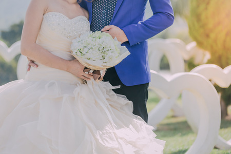 The bride and groom join hands and hold a beautiful bouquet on wedding day.