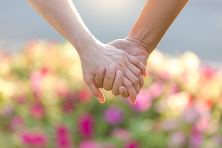 Closeup of loving couple holding hands while walking in the park at sunset
