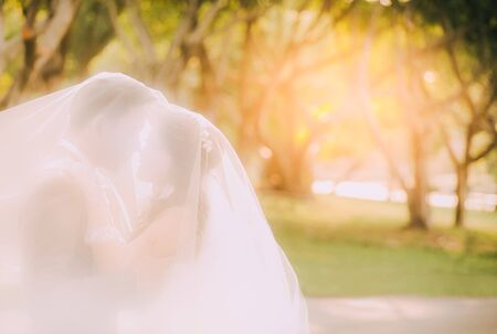 Smooth blur of bride and groom at sunset in wedding ceremony.