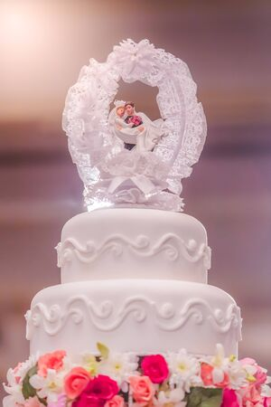 The wedding doll is on top of the wedding cake and has a soft backlight from the lamp in the back.