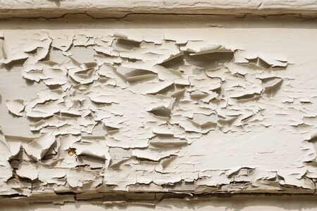 The surface of the paint that is old and peeling off.