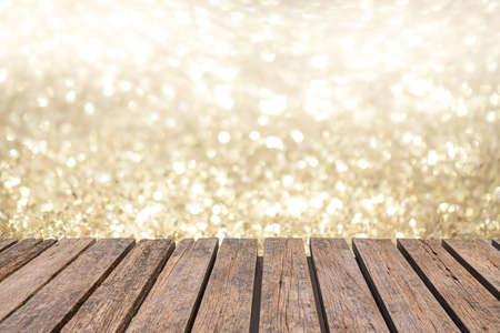 rustic old wood table in front of glitter silver and gold bright bokeh lights for display products. wall background.