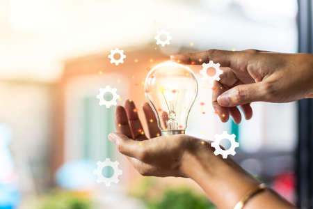 A hand with a light bulb Is a creative idea of innovation Abstract the concept of business success