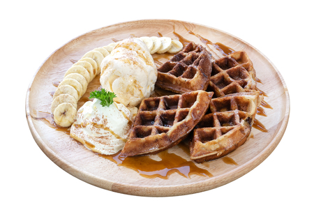 Brown waffle and ice cream with sliced banana in wood plate isolated on white background Stock Photo
