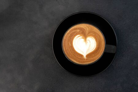 Top view of hot coffee cappuccino latte art heart shape foam in black cup on dark table background