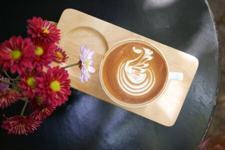 Hot coffee cappuccino latte art swan bird foam on wooden plate with flowers top view background Reklamní fotografie