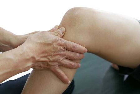 Physical therapist's hands treat knee and leg to the patient on white background
