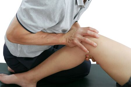 Physical therapist treats knee and leg to the patient on white background