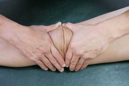 Physical therapist hands techniques treat knee on the patient leg to reduce pain Reklamní fotografie
