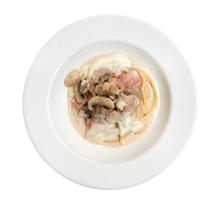 Italian pasta spaghetti carbonara with fried bacon in ceramic plate top view isolated on white background