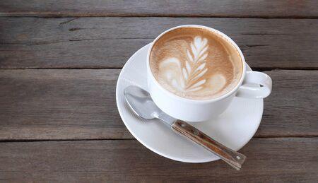 Hot coffee cappuccino latte art milk foam with spoon on wooden background Reklamní fotografie