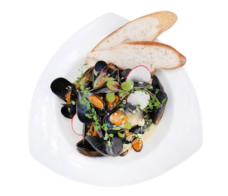 Steamed Mussels in white wine with two pieces breads in ceramic plate isolated on white background, clipping path included