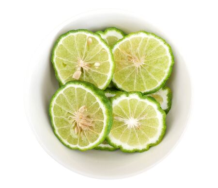 Green sliced bergamot kaffir lime balls herb in ceramic bowl isolated on white background, clipping path included
