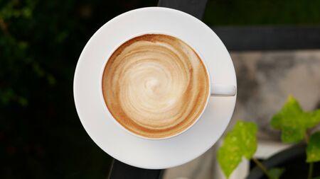 Hot coffee cappuccino latte art spiral foam in ceramic cup top view
