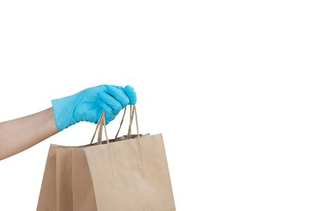 Hand wearing blue glove for protect allergic reaction or infectious diseases coronavirus/covid-19 holding paper bags deliver goods to customer isolated on white background, clipping path included Reklamní fotografie