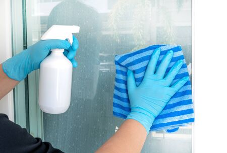 Hands wearing blue gloves holding a white plastic spray bottle and towel fabric cleaning home glass door for protect allergic reaction or infectious diseases coronavirus/covid-19. Reklamní fotografie