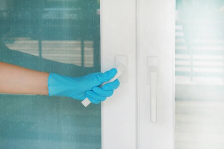 Hand wearing blue glove holding white door handle protecting allergic reaction or infectious diseases coronavirus/covid-19.
