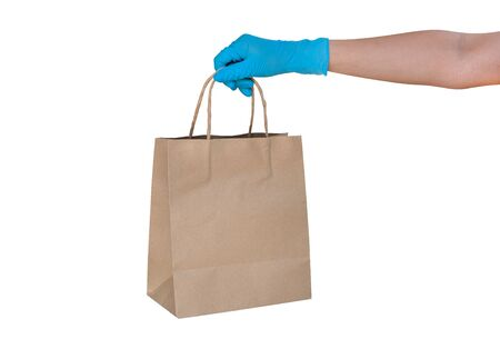 Hand wearing blue glove for protect allergic reaction or infectious diseases coronavirus/covid-19 holding paper bag deliver goods to customer isolated on white background, clipping path included